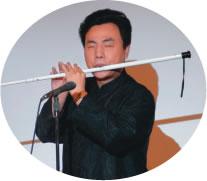 白杖に穴をあけた自作笛を演奏する楊さん
